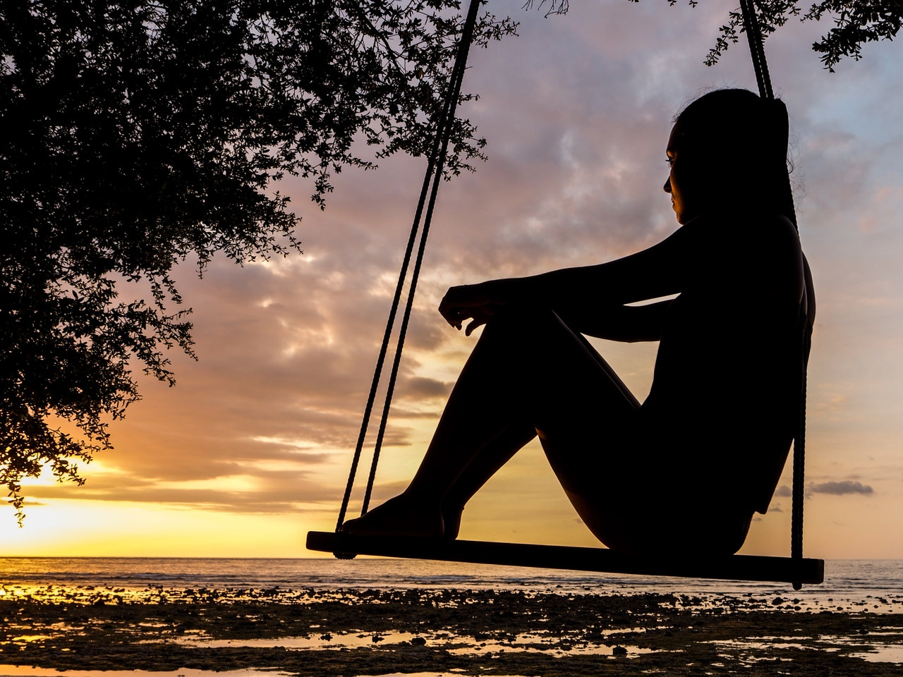 woman_sitting_on_swing_sunset